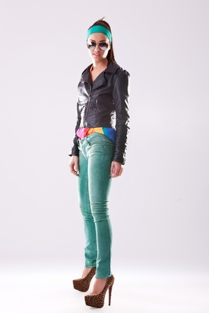 full length picture of a young woman in leather jacket and jeans looking at the camera photo