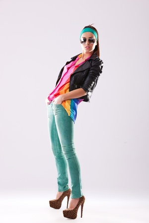 side view of a casual fashion woman in leather jacket and sunglasses standing with her hands in her pockets Stock Photo