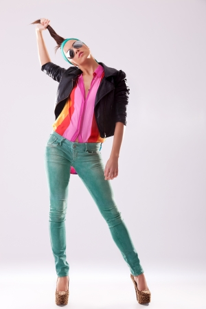 pulling hair: young woman in high heels and leather jacket pulling her hair Stock Photo