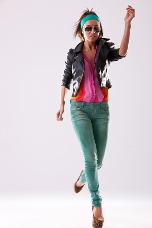 young fashion male model wearing sunglasses, jacket and high heels jumping photo