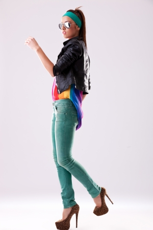 mezclilla: Vista lateral de una mujer joven casual en gafas de sol y zapatos de tacón alto, dando un paso adelante Foto de archivo