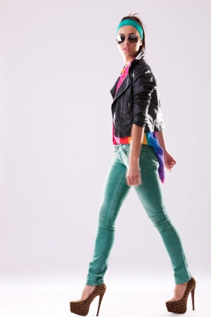 side view of a walking young woman wearing casual clothes, jacket and high heels and looking at the camera photo
