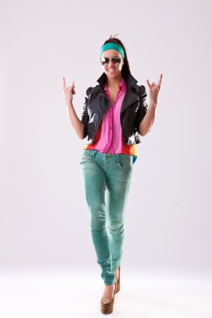Attractive young woman in sunglasses high heels and casual clothes making the rock and roll hands gesture photo