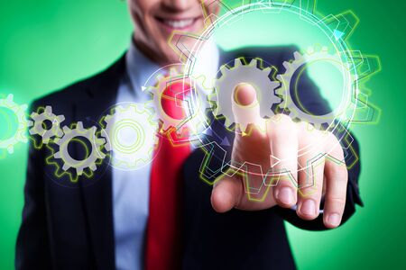 business man pushing wheels as symbols of engineering and design  Stock Photo - 15333353