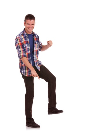giant man: Casual young man stepping on something, pointing at it and smiling. Young man posing like Goliath, showing his superiority