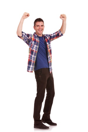 excited: Full body picture of an excited casual young man cheering with his hands raised in the air, isolated on white background