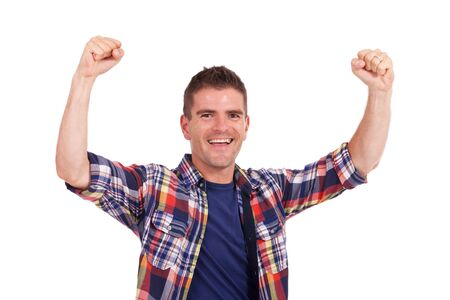 deserved: casual young man cheering with arms raised, after a deserved victory