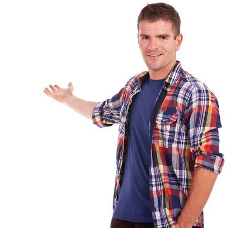 waistup: Waist-up picture of a young casual man presenting something in his back, with a hand in his pocket, smiling at the camera.