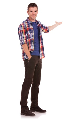 Young man dressed casual is presenting something while holding his other hand in his pocket. photo