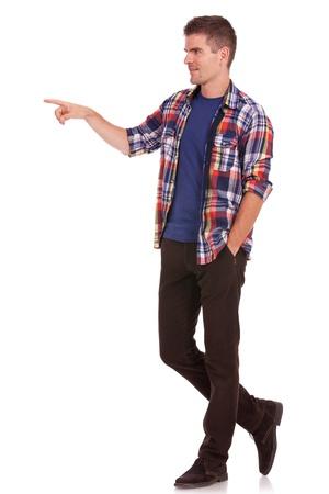 cuerpo entero: Casual hombre joven con la mano en el bolsillo, señalando y mirando en una dirección, lejos de la cámara. en el fondo blanco