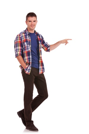 something: Full length photo of a casual young man pointing towards something and holding one hand in his pocket while looking at the camera. On white background