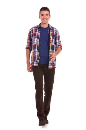 full length: full length picture of a casual friendly young man walking towards the camera – isolated over a white background