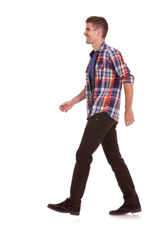 side view of a young casual man walking on a white background