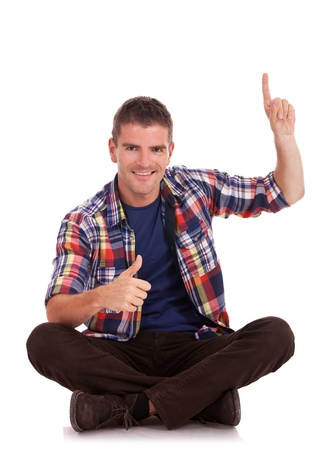 legged: Portrait of a casual young man sitting on the floor, legs crossed, giving the thumbs up and pointing upwards, all this with a big smile on his face.