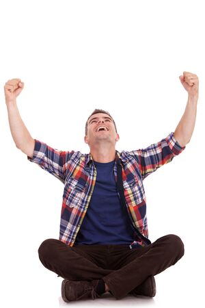 cross arms: Portrait of a young casual man sitting with legs crossed and cheering with arms and look raised