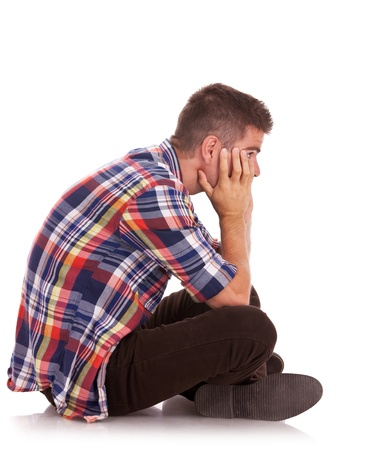 desesperado: vista lateral de un hombre joven casual sentado decepcionado con la cara entre las manos. aislado en blanco