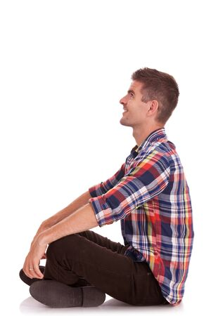 knees up: side view of a cross legged casual young man looking up, away from the camera and holding his hands on his knees Stock Photo