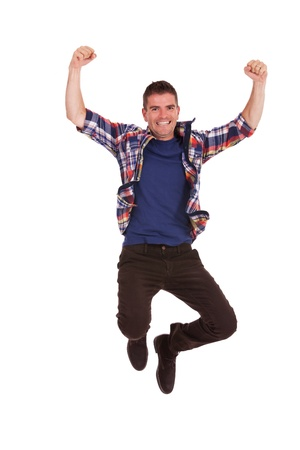 ecstatic: Picture of an ecstatic casual young man, jumping in the air and smiling, with hands raised