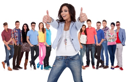 casual young woman making the thumbs up ok sign in fron of a group of young people smiling photo