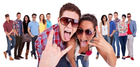 couple of very happy couple making the rock and roll gesture in front of a smiling group of casual people photo