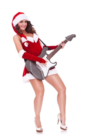 full length picture of a sexy santa woman playing an electric guitar and smiling to the camera on white background  photo