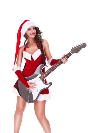 sexy young brunette woman wearing a Santas costume and playing a guitar with a smile on her face photo