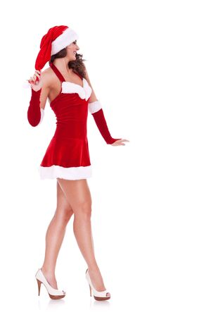 side view of a sexy young santa woman walking on a white background  photo