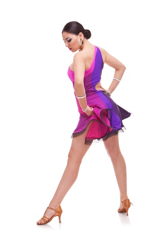 side view of a beautiful salsa dancer holding her pink dress and looking down Stock Photo