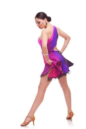 baile latino: Vista lateral de un bailar�n de salsa hermosa celebraci�n de su vestido rosa y mirando hacia abajo
