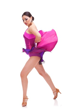 beautiful salsa dancer posing with her pink dress raised photo
