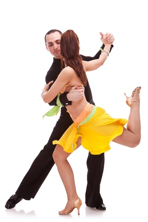 nice salsa dancing couple with the woman holding one leg in the air, looking away from the camera photo