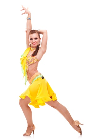 appealing salsa dancer in a nice dance pose. she is holding a hand stretched upward and the other behind her head Stock Photo