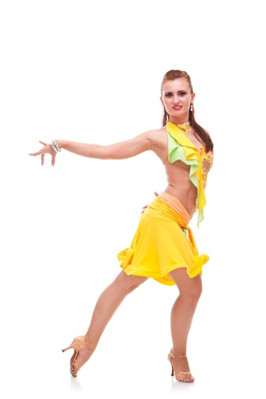 portrait of a salsa dancer standing in a dance pose with her hand stretched to a side and looking into the camera photo