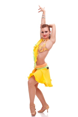 rumba: full length picture of a passion salsa dancer wearing a yellow dress and posing in a dance move