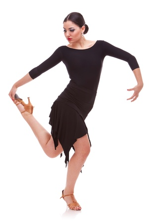 tangoing: beautiful young salsa dancer holding her leg in a dance pose