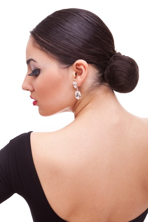 back view of a gorgeous young salsa woman dancer with black dress, looking sensually to a side  photo