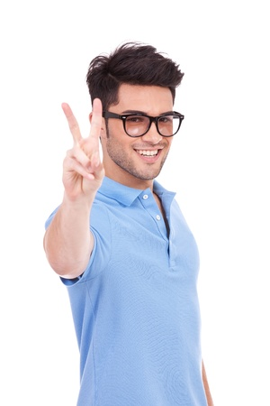 handsome young man showing victory or peace sign, isolated on white background  photo