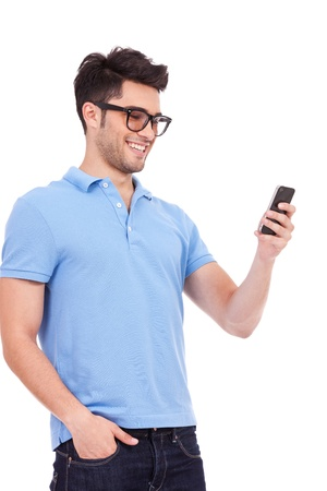 Young casual man reading something on his phone and smiling photo