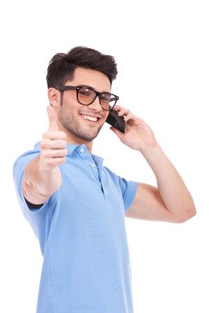 human pile: Astuto uomo casual giovane parla al telefono e mostrando thumbs up gesto, mentre sorride alla macchina fotografica. isolato su bianco