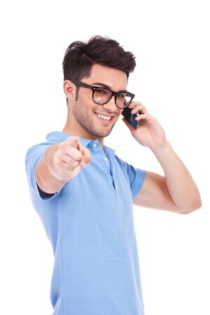 waistup: waist-up picture of an attractive young casual man with eyeglasses pointing and looking at the camera while speaking on the phone