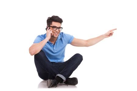 persona sentada: Fotograf�a de un hombre joven casual sentado con las piernas cruzadas, hablando por tel�fono y apuntando a su lado, mientras sonriendo a la c�mara.