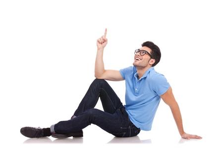 ascending: foto de un hombre joven casual tirado en el suelo. est� se�alando y mirando hacia arriba con una sonrisa en su rostro.