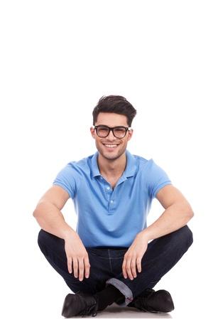 persona sentada: joven casual con gafas sentado en el suelo con las piernas cruzadas y sonriendo Foto de archivo