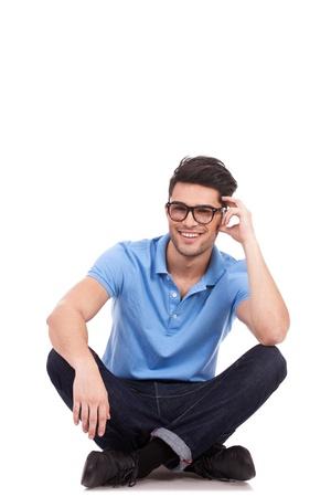 hombre sentado: casual hombre joven sentado con las piernas cruzadas y sosteniendo su cabeza mientras sonreía a la cámara aislada en blanco