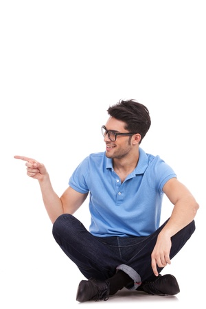 sideways: appealing casual young man sitting on the floor, pointing and looking to his side while smiling