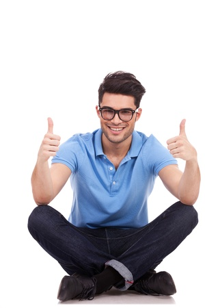 agree: casual young man sitting cross legged showing thumbs up with both hands and smiling to the camera