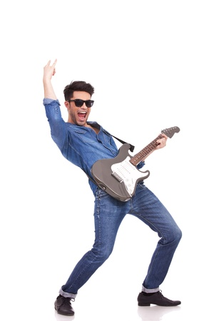 hardrock: young casual man performing on an electrical guitar and screaming, against a white background Stock Photo