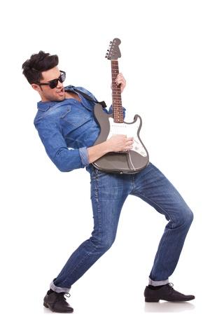 m�sico: Imagen de cuerpo entero de un joven guitarrista funcionando muy apasionadamente sobre un fondo blanco