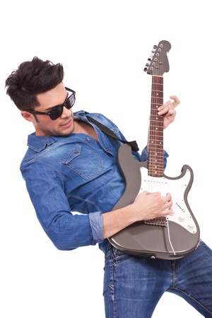 bass player: young casual man playing passionately his electric guitar, over white background Stock Photo