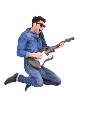 agressive: casual young man jumping and shouting while playing an electric guitar, isolated on white